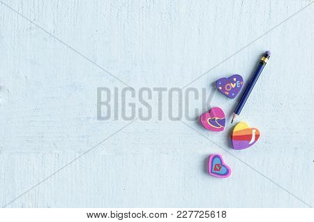 Different  Eraser In The Shape Of A Heart With A Pencil On Blue Background With Space For Text
