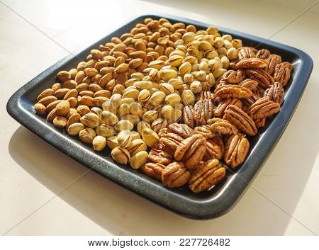 Nuts Almonds, Pistachios And Pecans On Black Plate, Close-up, Set.