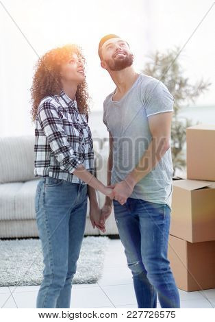 Young couple standing in new apartment and looking up