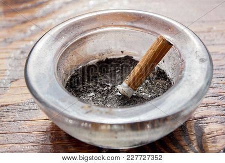 Cigarette With Ashtray On Wood Table Close Up