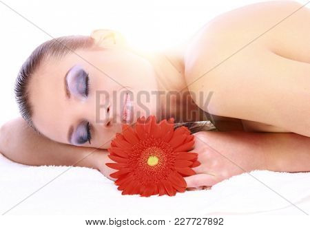 Young beautiful woman relaxing with flower at spa isolated