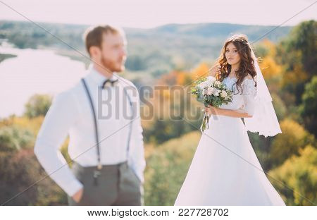 Stylish Bride And Groom Posing On The Background Of The River. Wedding Couple