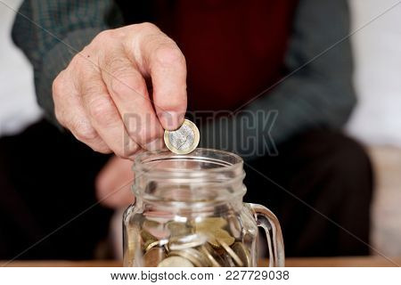 closeup of an old caucasian man saving a one euro coin in a glass pot