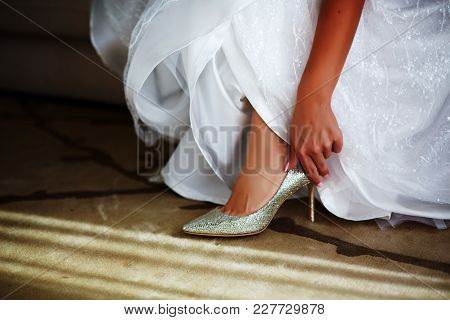 Bride In White Wedding Dress Putting On Silver Shoes