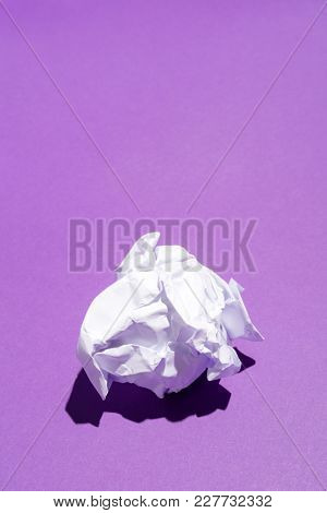 Creased sheet of white paper laying on a vivid violet background. Paper recycling concept.