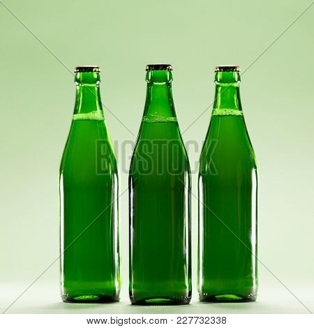 Three green bottles on a light green background. Craft beers. St Patrick's Day. Irish culture.