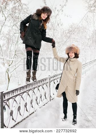 Adorable Happy Young Brunette Women Holding Hands In Fur Hat Having Fun Snowy Winter Park Forest In