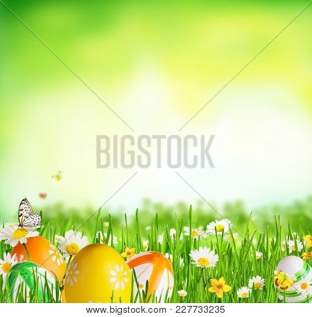 Idyllic spring meadow with Easter eggs and butterflies with green background. Spring concept with copyspace.