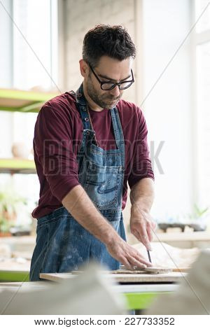 Ceramist Dressed in an Apron Cutting the Pieces of Raw Clay in the Bright Ceramic Workshop.