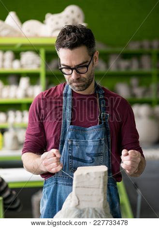 Ceramist Dressed in an Apron Working with Raw Clay in the Bright Ceramic Workshop.