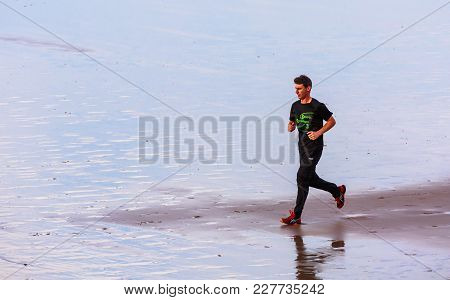 Henday, France - Sept 26, 2016:side View Of A Young Man Doing His Jogging Alone On The Beach At The