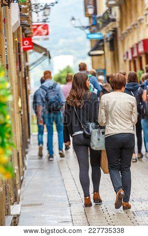 San Sebastian, Spain - September 27, 2016:focus On Two Casual Women Walking On A Pedestrian Street W