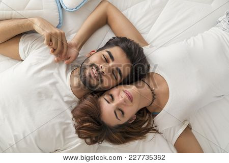 Top View Of A Young Couple In Love Lying In Bed, Cuddling After Waking Up