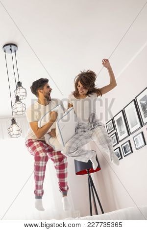 Happy Loving Couple Having Fun While Jumping On Bed. Focus On The Girl