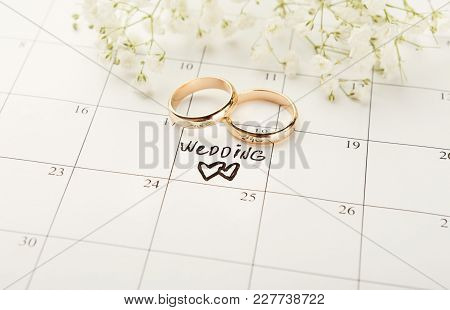 Word Wedding, Two Hearts And Gold Rings On Calendar With Sweet White Flowers. Love, Invitation, Adve