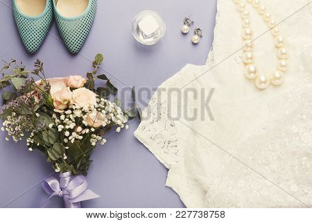 Wedding White Dress, Accessories, Blue Shoes And Bride Bouquet On Purple Background With Copy Space,