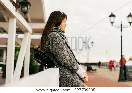 Stylish Dark-haired Girl In Gray Coat Walking Through City Streets Posing