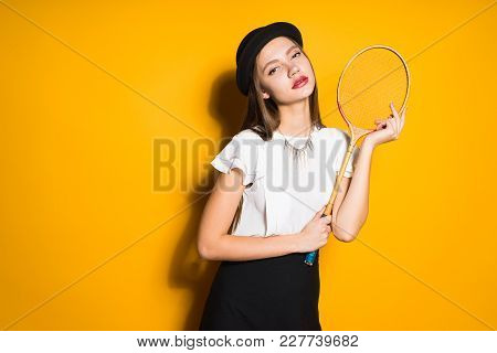 Attractive Girl In A Black Hat Posing On A Yellow Background, Holding A Tennis Racket