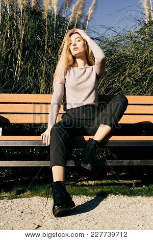 Stylish Young Blonde Girl Sits On A Bench Outdoors, Posing In The Sun