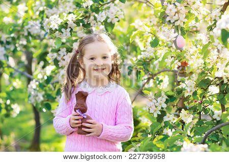 Kids On Easter Egg Hunt In Blooming Garden.
