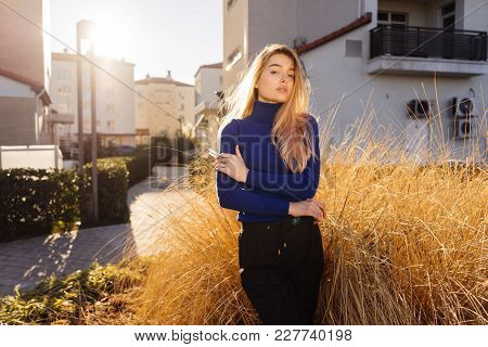 Attractive Young Blonde Girl In Trendy Blue Sweater Posing In The Sun, Street Style
