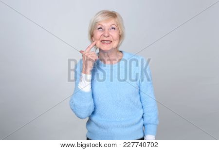 Happy Adult Woman Is Pointing A Finger At Her Cheek. Gesture With Your Finger Where You Need To Kiss