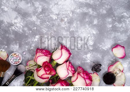Frame Of Roses And Decorative Cosmetics As Frame On A Stone Background With Copy Space. Styled Woman