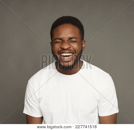 Black Man Laughing On Grey Background, Studio Shot, Copy Space