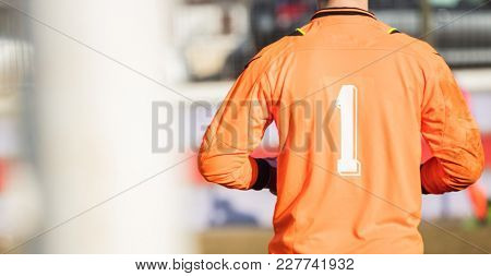 Football Soccer goalkeeper with orange color uniform and number one, from behind view. Abstract backdrop, close up, details, banner, space.