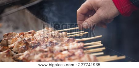 Meat skewers souvlaki on barbecue. Man's hand turns on the other side the skewers on grill. Close up, front view, banner.