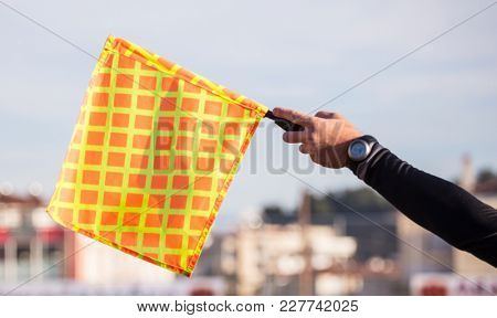 Football soccer arbiter assistant observes the match and raises the flag with his hand. Blurred blue sky and buildings background, close up view.