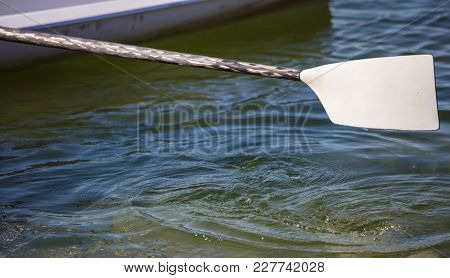 A side of boat and a white oar ready to touch the swirl sea. Blue sea background, close up view with details, empty, space for text.