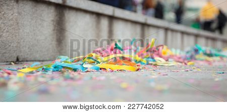 Carnival party with colorful serpentines on street. Blurred pavement background. Close up view, banner, space for text.