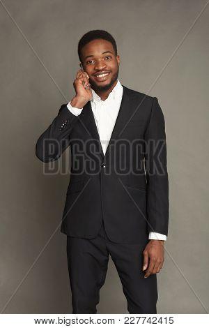 Happy Young Black Man Portrait In Formal Wear Talking On Smartphone At Grey Studio Background, Crop