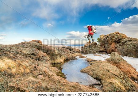 a male backpacker on a mountain ridge in winter scenery - Horsetooth Rock trail above Fort Collins in northern Colorado