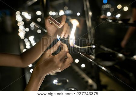 Woman Is Lighting A Wick On The Blurry Background Of The Burning Candles In The Buddhist Temple In K
