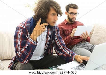two guys sitting on the couch, talking on a mobile phone and chatting on the Internet.