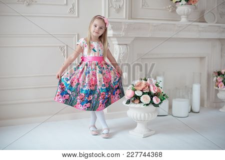 Full-length Of Little Smiling Girl Child In Colorful Dress Posing Indoor.