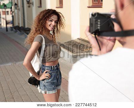 Beautiful brown curly hair  woman posing in city