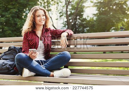 Beautiful Smiling Female Sitting And Listening To Music On The Smartphone On The Bench Outdoors. Tec