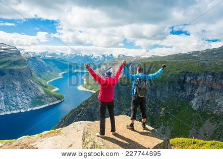 Couple Posing On Trolltunga. Happy Woman And Man Enjoy Beautiful Lake And Good Weather In Norway.