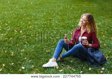 Beautiful Smiling Female Listening To Music On Smartphone While Sitting On The Grass Outdoors. Techn