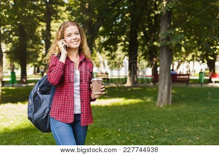 Beautiful Smiling Female Student Talking On Mobile While Standing In Park Outdoors. Technology, Soci