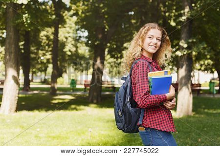Happy Young Student Girl Standing In The Park, Holding Notebooks And Backpack Behind Her Shoulders.