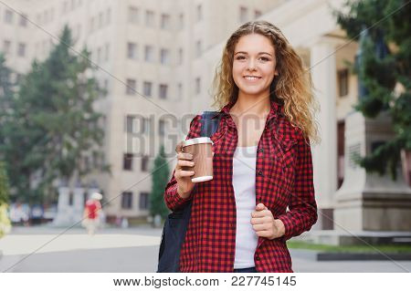 Beautiful Smiling Female Student Holding Coffee Cup While Standing In Front Of The University Campus