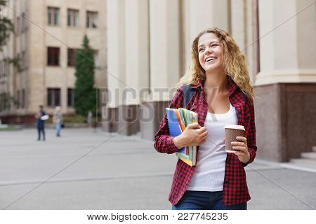 Beautiful Smiling Female Student Holding Notebooks And Smartphone In Hands While Standing In Front O