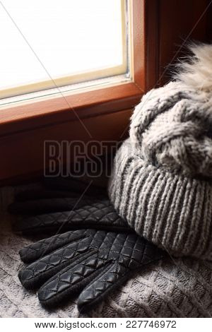 Grey Knitted Woolen Scarf, Gloves And Hat With Fur Pompon On Windowsill. Winter Still Life Backgroun