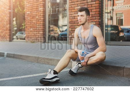 Young Pensive Man Runner Is Having Break, Drinking Water While Jogging In City, Sitting On Floor And