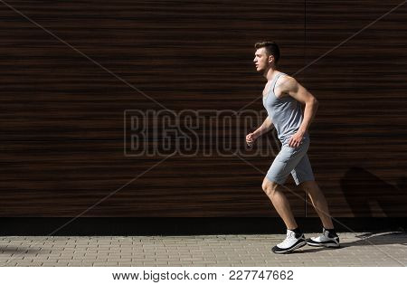 Young Man Running In City, Dark Wooden Wall Background, Copy Space