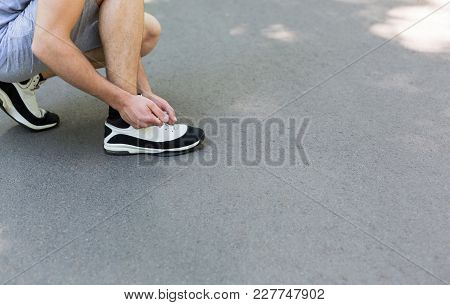 Unrecognizable Man Tying Shoelaces On Sneakers Before Running, Getting Ready For Jogging In Park, Cl